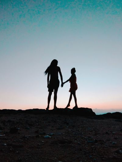 Silhouette friends standing on street against sky during sunset