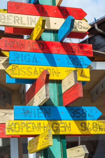 Wooden signpost with directions and distance to capital cities in Europe Cities In Europe Close-up Communication Day Destination Direcctions To Direction Discover Your City Hanging Information Sign Multi Colored No People Outdoors Signpost Text Travel Destinations Wooden Postsigns
