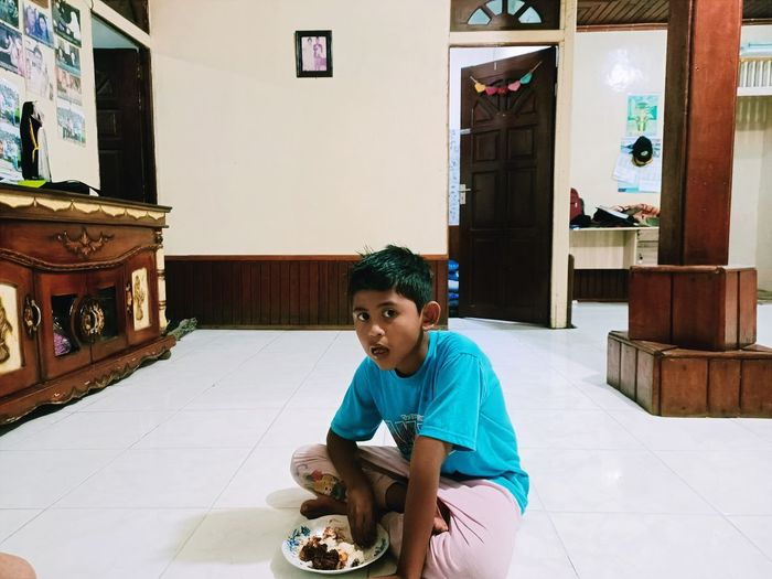 Portrait of boy eating food while sitting on floor at home