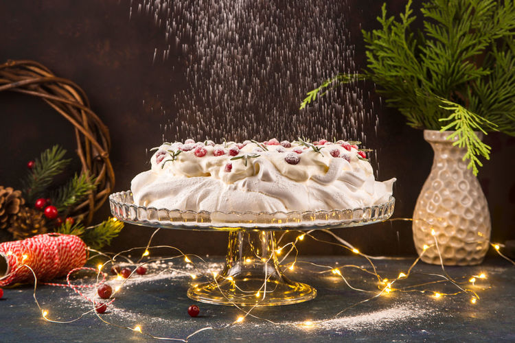 View of cake with christmas lights and plant against black background