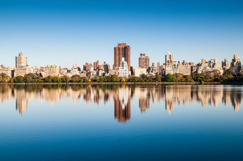 View of buildings on fifth avenue from across Jacqueline Kennedy Onassis Reservoir in Central Park, NYC Water Architecture Sky Built Structure Building Exterior Waterfront Reflection City Building Clear Sky Blue No People Lake Day Urban Skyline Cityscape Central Park