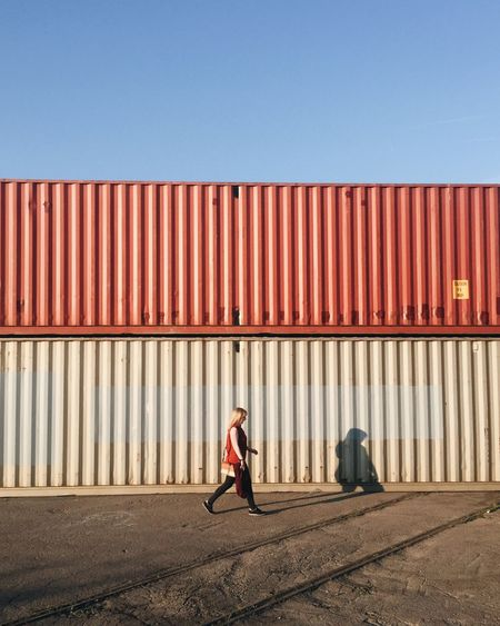 Full length of woman walking against cargo container during sunny day