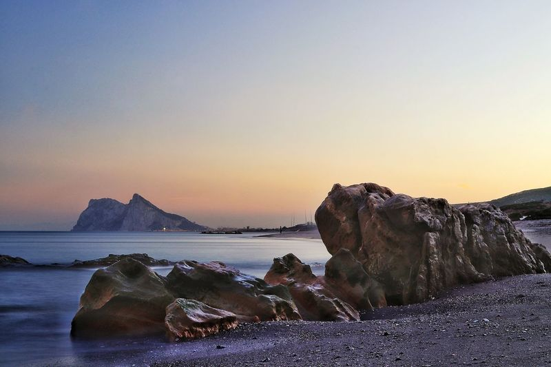 A twilight view of Gibraltar taken from the beach in Alcaidesa with rocks in the foreground Beach Photography Gibraltar Landscape Gibraltar Rock Gibraltar Views Gibraltar And Sea Beach Beach Scene  Beauty In Nature Clear Sky Gibraltar Gibraltarview Horizon Over Water Nature No People Rock - Object Scenics Sea Sky Sunset Tranquil Scene Tranquility Twilight Sky Twilight View Twilightscapes Water