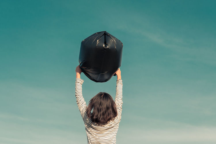 Rear view of girl holding garbage bag against sky