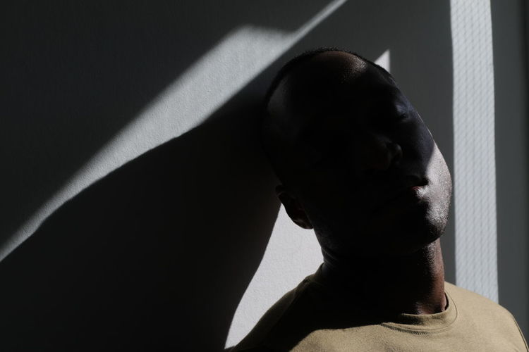 Close-up portrait of man against wall