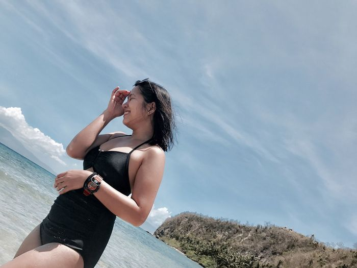 Side view of young woman in swimwear standing at beach against sky during sunny day