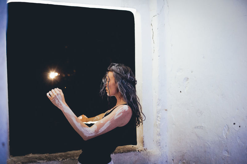 Woman covered in paint while standing against window at night