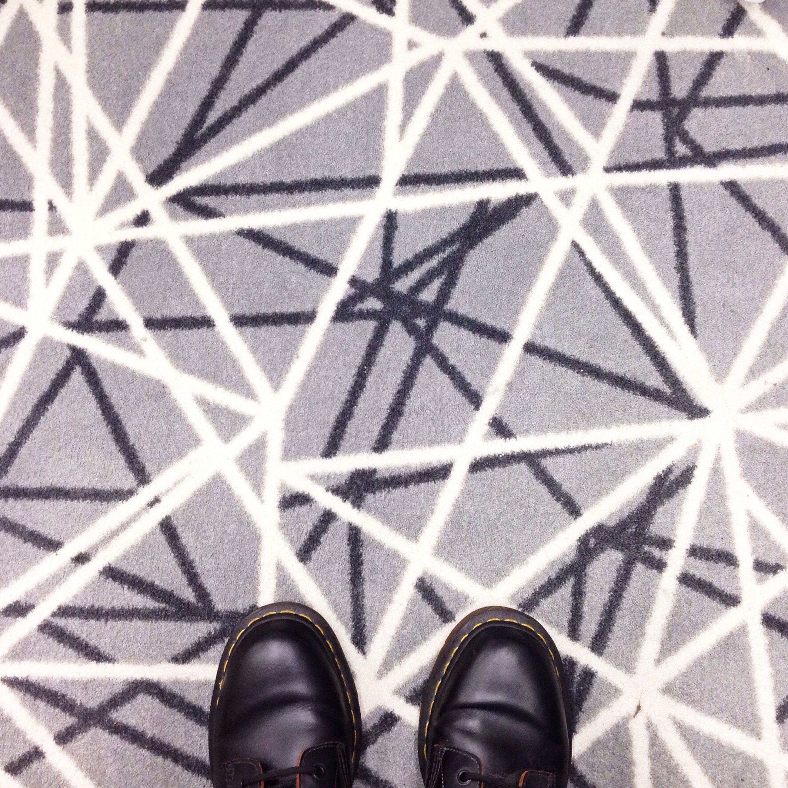 low section, indoors, pattern, person, personal perspective, lifestyles, shoe, men, leisure activity, standing, unrecognizable person, tiled floor, design, human foot, high angle view, flooring