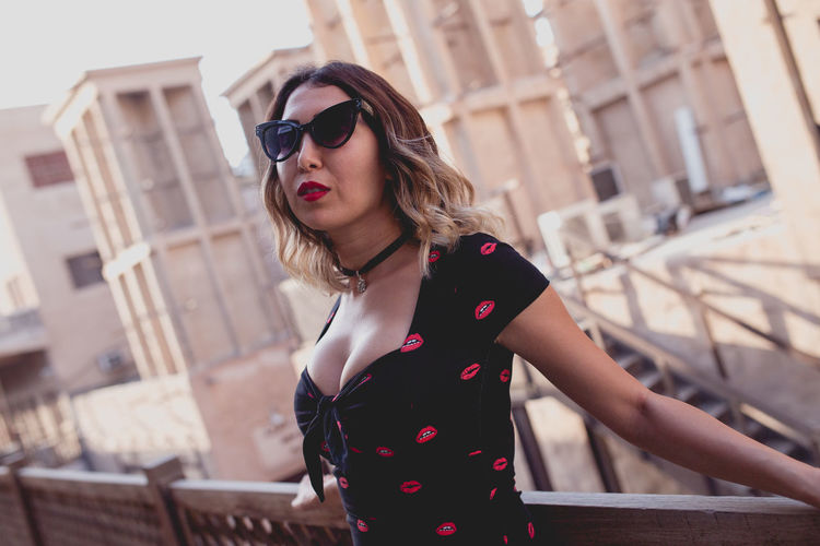 Portrait of young woman wearing sunglasses standing by railing in city