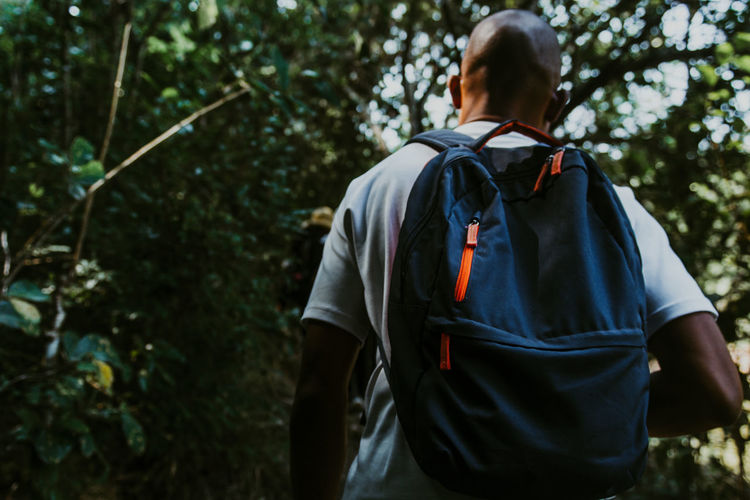 Rear view of man walking in forest with a backpack