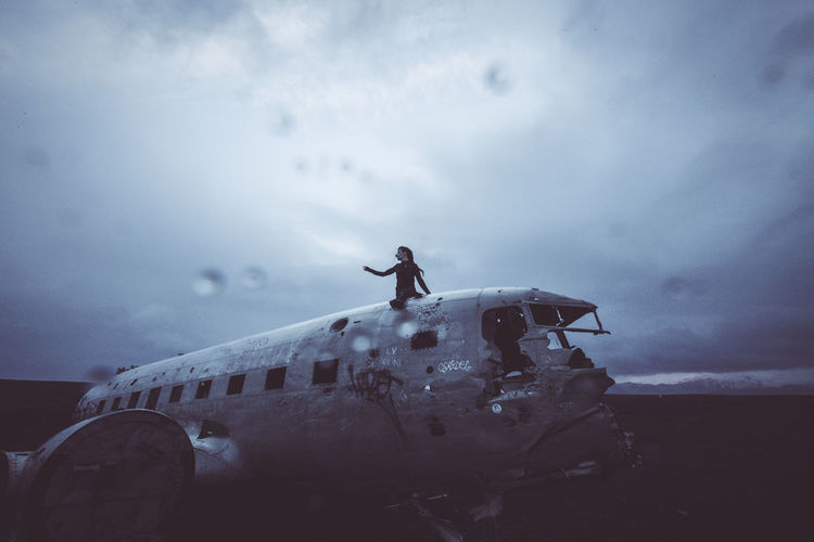 Woman sitting on abandoned airplane against sky