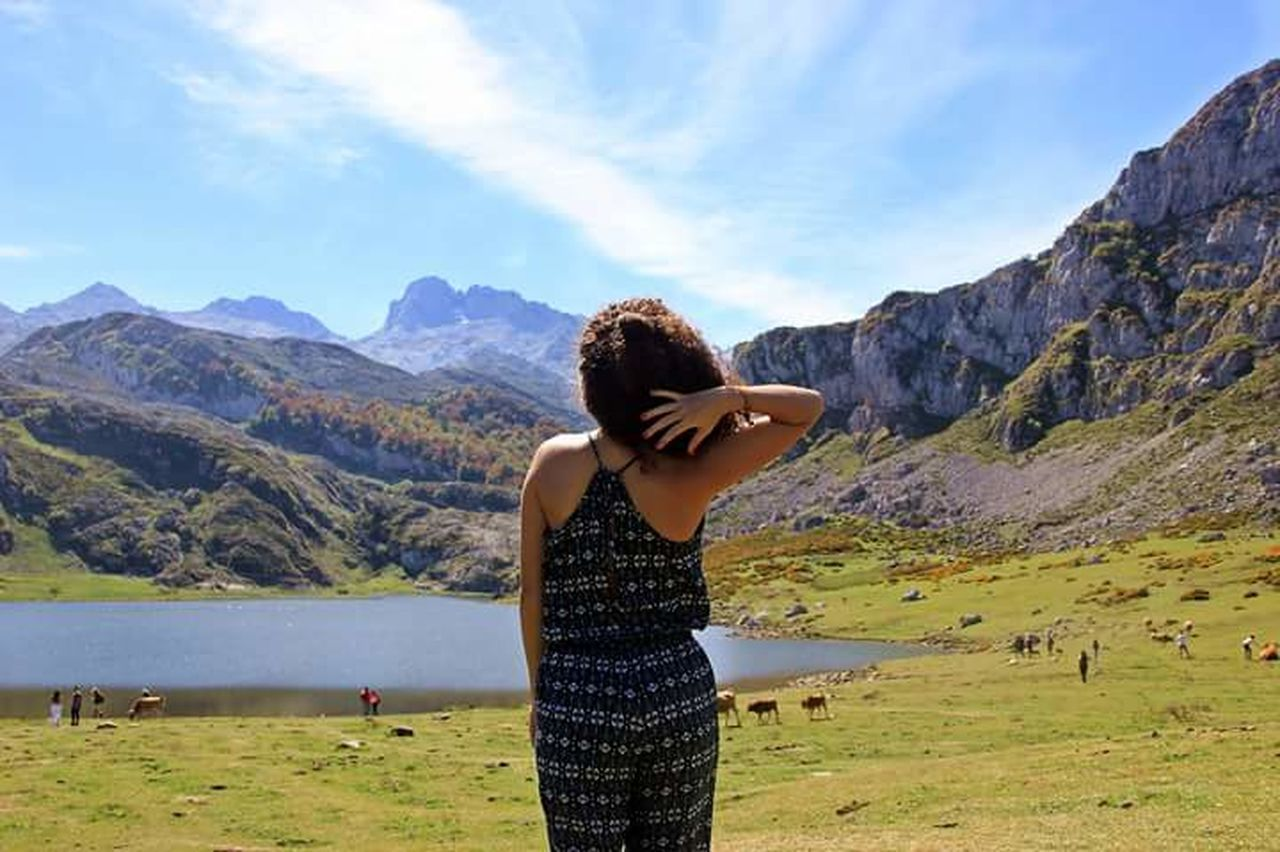 mountain, real people, leisure activity, lifestyles, one person, sky, scenics, mountain range, nature, beauty in nature, casual clothing, standing, day, young women, young adult, outdoors, cloud - sky, landscape, water, women