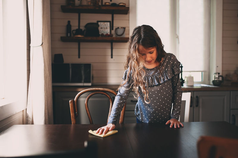 happy kid girl helping with housework and cleaning table in the kitchen One Person Indoors  Real People Lifestyles Home Interior Child Kid Childhood Girl Daughter Help Helper Cleaning Housework Table Kitchen Dust Funny Home
