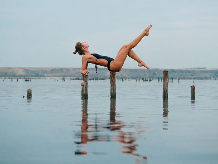 Water Real People Shirtless Leisure Activity Two People Lifestyles Full Length Waterfront Nature Day Young Adult Sea Barefoot Young Women Outdoors Handstand  Men Jumping Beauty In Nature Sky