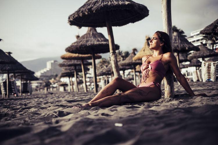 Woman in bikini sitting at beach