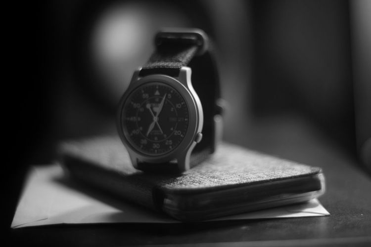 Close-up of wristwatch with mobile phone on table