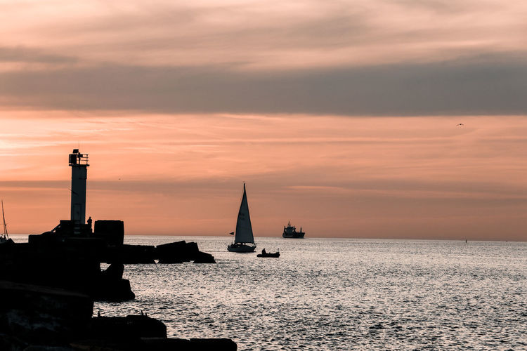 Silhouette sailboats in sea against sky during sunset