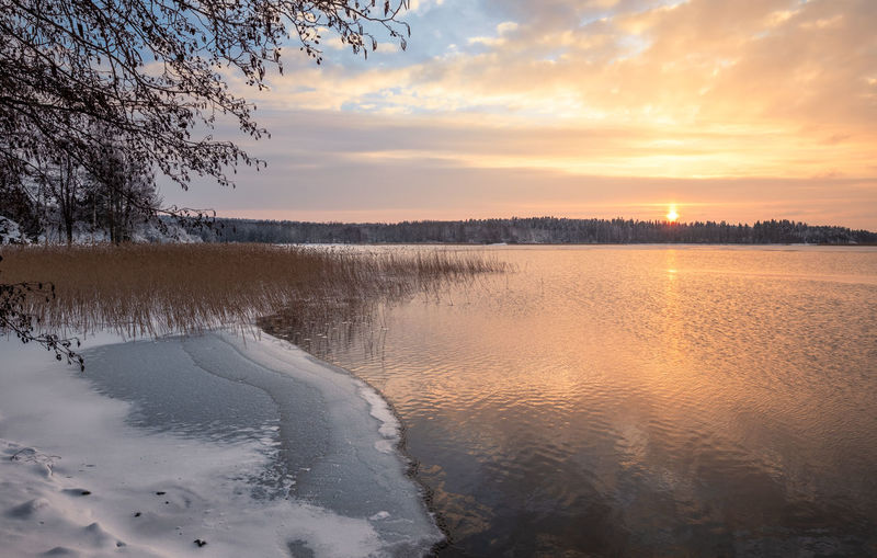 Scenic winter landscape with sunset at icy and peaceful lake in Finland Sky Scenics - Nature Beauty In Nature Sunset Cloud - Sky Winter Tranquility Cold Temperature Tranquil Scene Tree Snow Nature Non-urban Scene No People Finland Sunrise Landscape Mountain Tranquility Peaceful Nature Orange Color Colorful Winter Ice