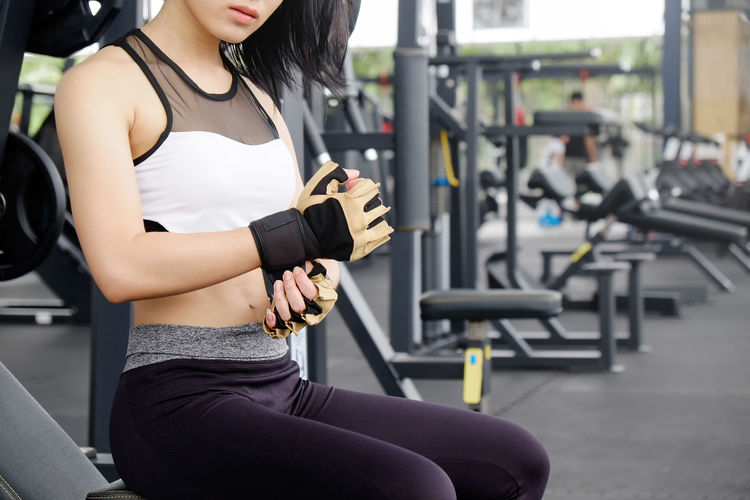 Young Woman Wearing Sports Gloves In Gym