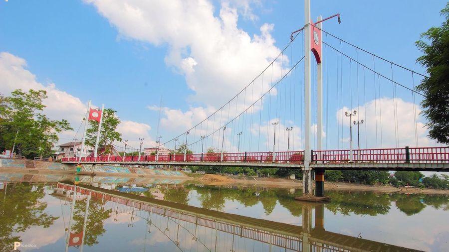 Panoramic View Of Bridge Against Cloudy Sky