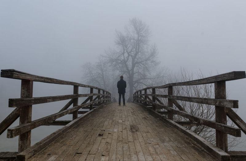 Rear view of man standing on footbridge