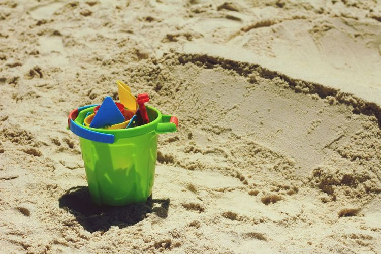 High angle view of bucket with toys on sand at beach
