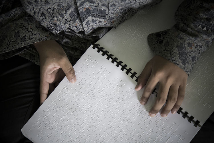 Midsection of blind person reading bible in braille