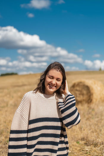 Portrait of smiling young woman standing on field