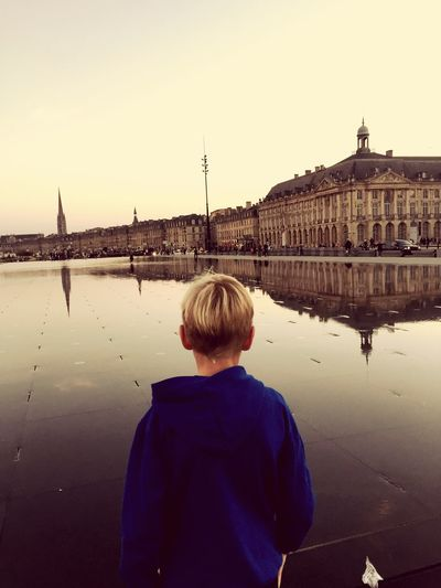 Rear view of boy standing on wet street while looking at buildings in city