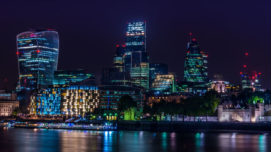 Illuminated cityscape by thames river at night