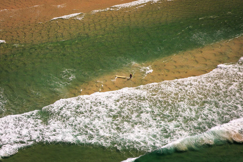 Aerial view of man surfboarding on sea