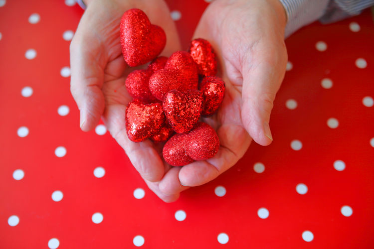 A man with both hands filled with glittery red hearts over a red and white polka dot background Celebration Hands Holiday Love Polka Dots  Shiny Textures Valentine's Day  Affection Cheerful Close-up Colorful Day Fingers Fondness Glittery Hearts Holding Indoors  One Person Pattern People Red Red And White Studio Shot