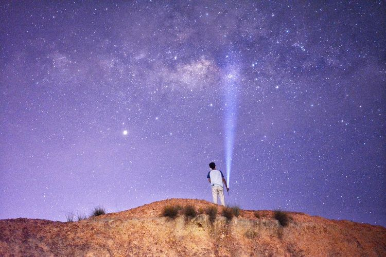 Rear view of man holding illuminated flashlight while standing on land against sky at night
