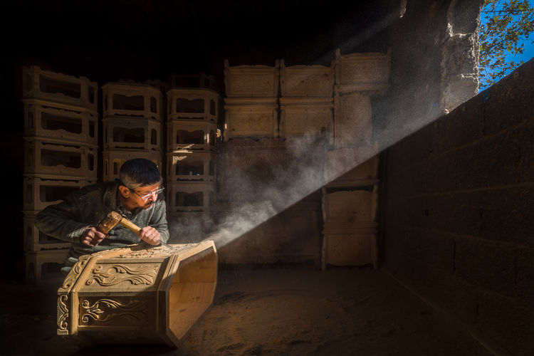 Sunlight falling on man carving wood in workshop