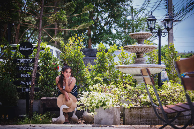 Young woman sitting on plant against trees