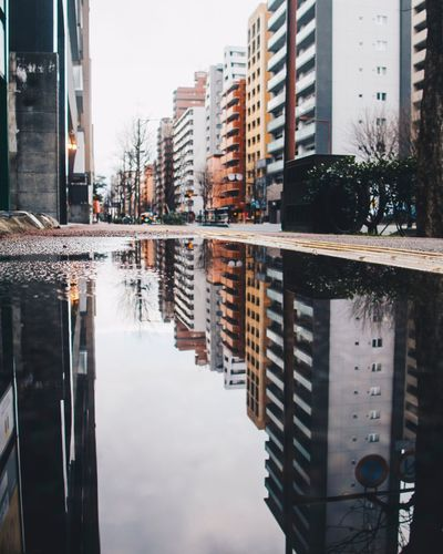 Reflection Of Buildings On Puddle At Street