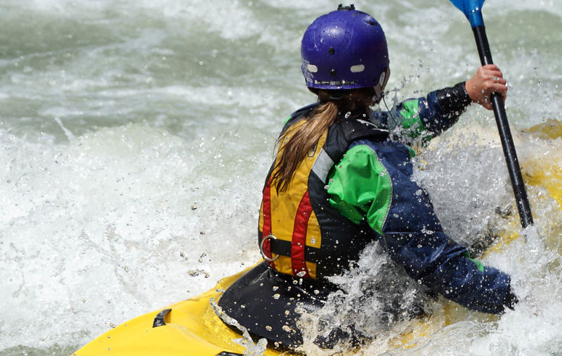 Rear View Of Woman Kayaking In River