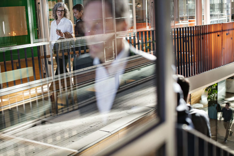 Blurred motion of people walking on railing
