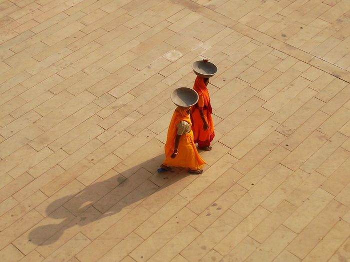 High Angle View Real People Flooring Day Clothing Sunlight Footpath Women Street Two People Outdoors Arts Culture And Entertainment Tiled Floor Orange Clothes Workers India Rajasthan Rajasthani Culture Sunset Long Shadow - Shadow Bowl Sari