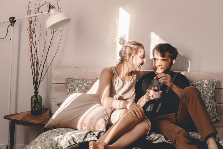 Couple having strawberry while sitting on bed at home