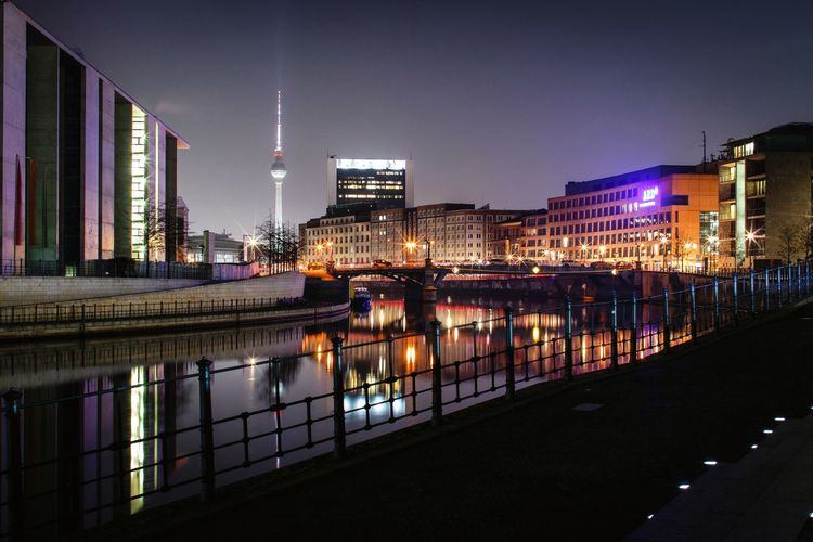 River passing through city buildings at night
