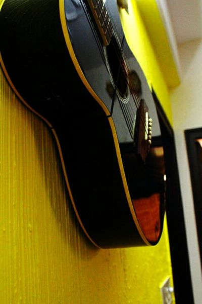 Summer Vacations My Point Of View Yellow Wall Peek Inside My Home Check This Out Different Angle Hanging On The Wall Music Instrument Close Up Photography Selective Focus Music Photography  Yellow Guitar Home Interior