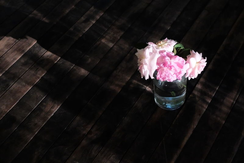 High angle view of pink flowers in vase on wooden table