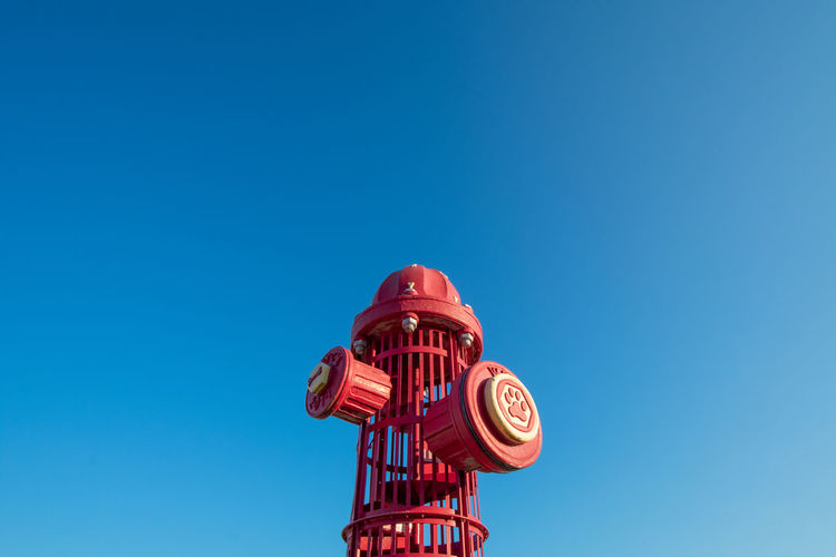 A giant red fire hydrant at a dog park on a clear sky