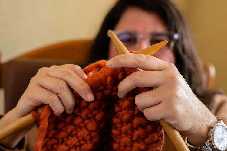 Close-up of woman knitting wool at home