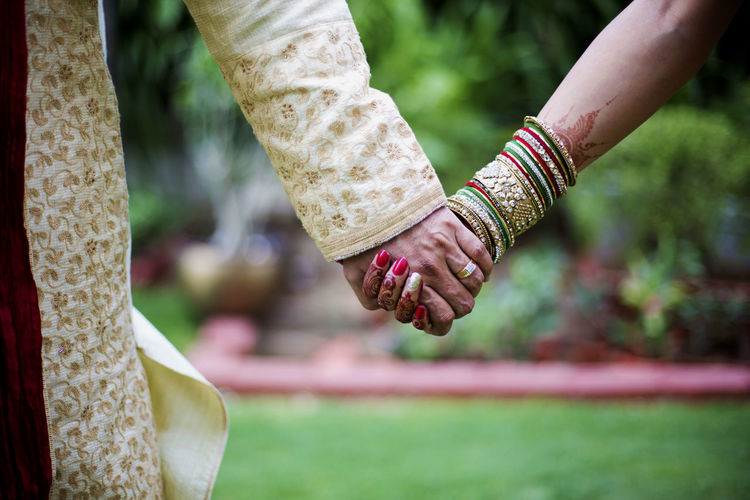 Close-Up Of Bride And Groom Holding Hands