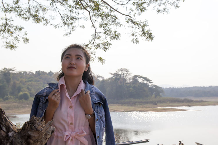 Beautiful young woman standing by lake against clear sky