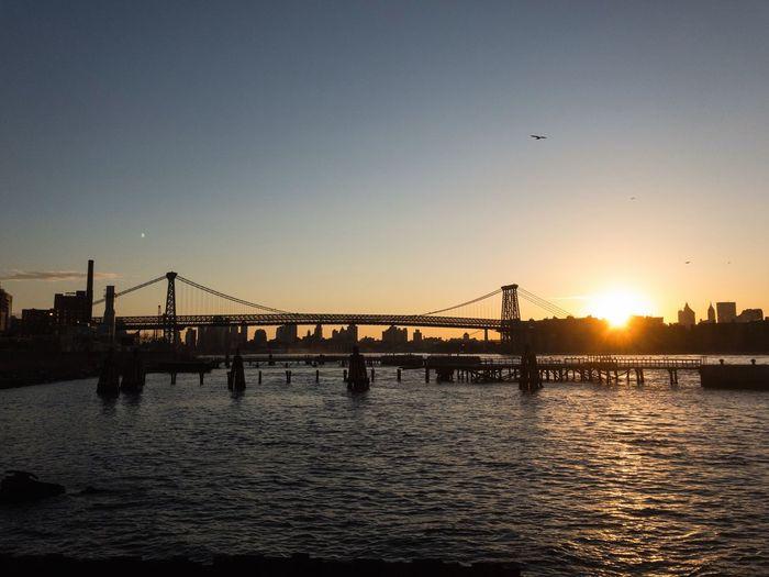 Silhouette of suspension bridge in city at sunset
