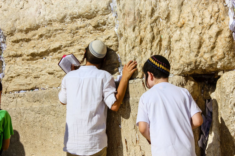 kids praying front the western wall Boys Cap Child Childhood Clothing Day Group Of People Hat Leisure Activity Males  Men Nature Outdoors People Real People Rear View Standing Stone Wall Waist Up Wall - Building Feature