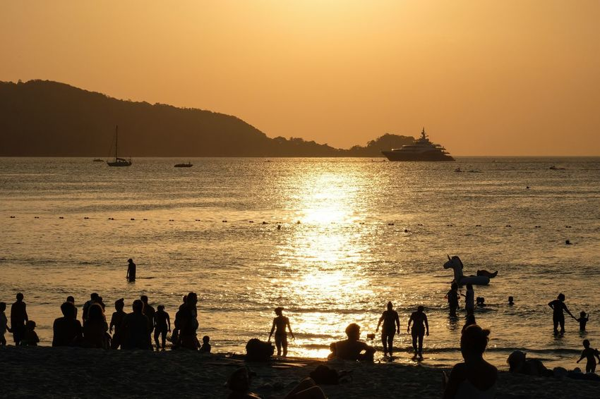 The beach Sunset Silhouette Water Sea Beauty In Nature Nature Scenics Beach Large Group Of People Lifestyles Nautical Vessel Vacations Real People Mountain Sky Outdoors Leisure Activity Sunlight Travel Destinations Men
